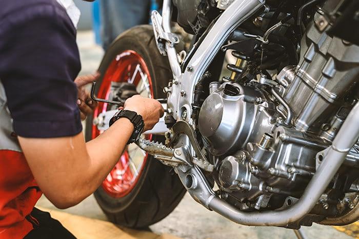 Motorradmechaniker repariert Stossdämpfer und Federbein